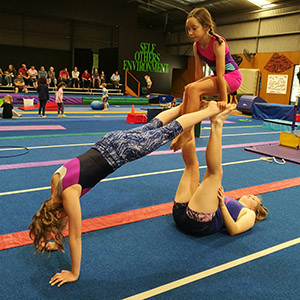 acro trio tuck sit on feet with middle in front support